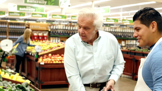 Mid-adult Hispanic male supermarket employee helps senior Caucasian male customer select peppers