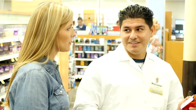 Mid-adult Hispanic pharmacist assists mid-adult Caucasian customer in supermarket pharmacy