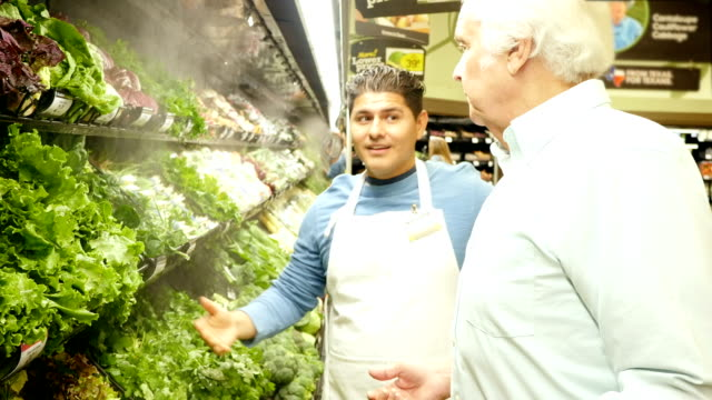 mid-adult hispanic supermarket employee explains different types of lettuce to senior caucasian male - mid adult men stock videos & royalty-free footage