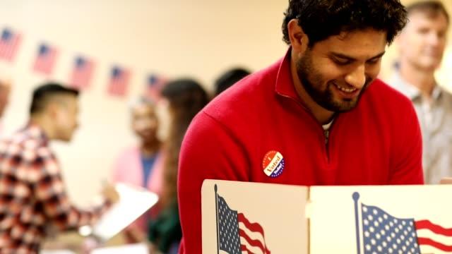 vídeos y material grabado en eventos de stock de el hombre de ascendencia latina y mitad de adulto vota en las elecciones de estados unidos. - latin american and hispanic ethnicity