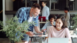 Mid-adult man having discussion with Asian woman in modern office