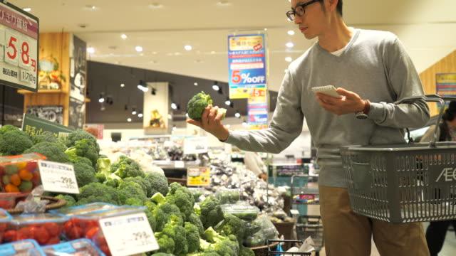 新鮮な野菜を買い物中の大人男 - 買う点の映像素材/bロール