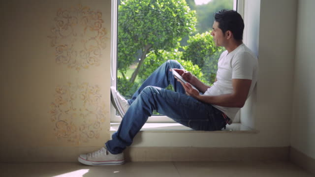ws mid-adult man sitting on window sill, using tablet pc / india - window sill stock videos and b-roll footage