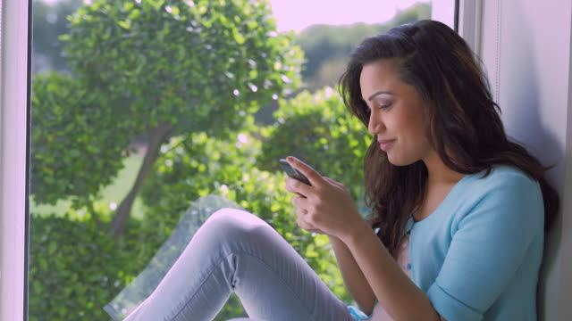 vídeos de stock e filmes b-roll de ms mid-adult woman texting by window / india - fotografia de três quartos