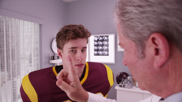 Mid-aged doctor examining football player after concussion