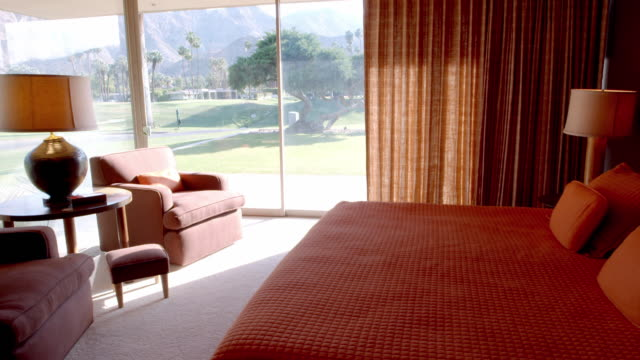 TS mid-century modern bedroom with floor-to-ceiling glass window and slider door overlooking country club golf course