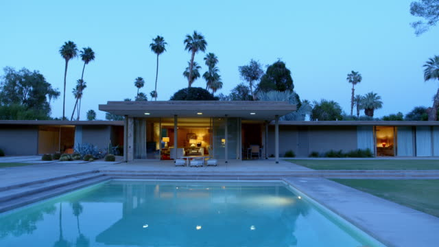 WS TS mid-century modern country club house with swimming pool at dusk and floor-to-ceiling glass slider doors allowing full view of living room with evening lights turned on