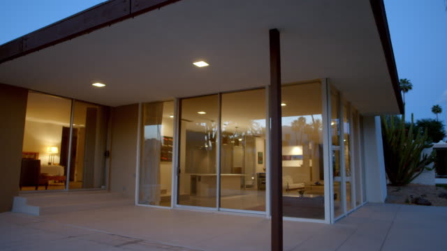 pan ts mid-century modern home at dusk with floor-to-ceiling glass windows and view of mid-century modern furnished living room and bedroom interiors, while sheltered by deep roof overhangs extending from flat roof - modern bedroom stock videos & royalty-free footage