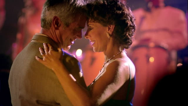 vídeos de stock e filmes b-roll de ms middle age couple slow dancing, talking + smiling on dance floor in nightclub / man kisses woman - casal de meia idade