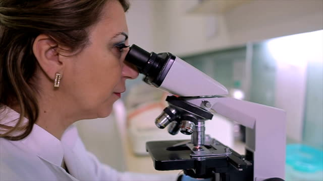 middle age female doctor in microbiology lab looking through microscope - antibiotic stock videos and b-roll footage