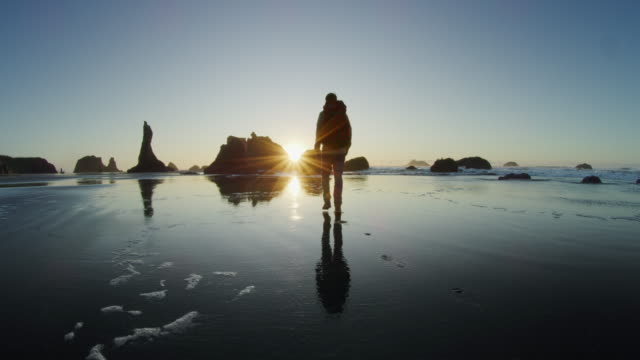middle age man hiking on beach at sunset, bandon oregon - 大自然威力 個影片檔及 b 捲影像