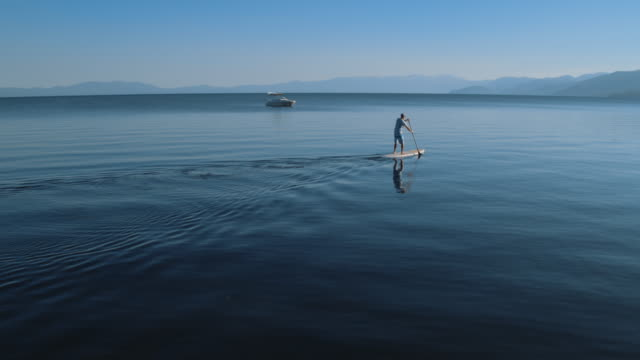middle age man paddleboarding on lake tahoe - pagaiare video stock e b–roll