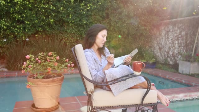 stockvideo's en b-roll-footage met middle age woman doing crossword puzzle by pool in the morning - puzzel