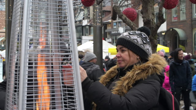 middle age woman heating her hands on a flame set in the park for that purpose. the temperature is of about minus 8 degrees celcius. bloor-yorkville... - arts culture and entertainment stock videos & royalty-free footage