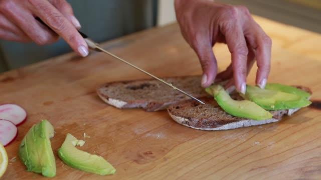 vídeos y material grabado en eventos de stock de middle age woman making avocado toast - aguacate