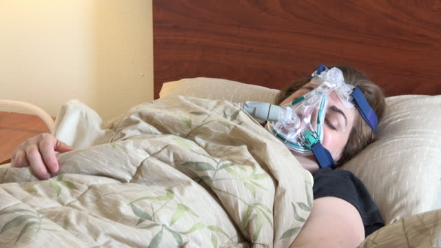 middle age woman suffering from sleep apnea; she wears a cpap mask - sleep apnea stock videos and b-roll footage