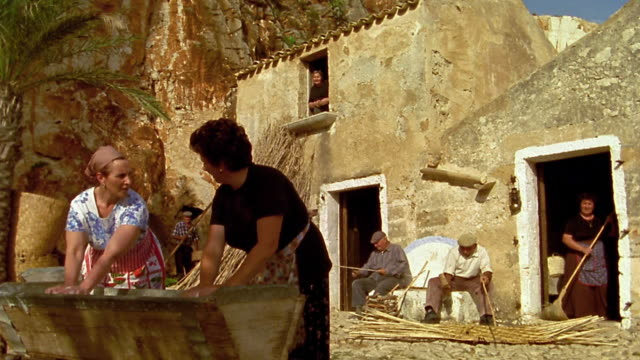 MS 2 middle age women washing clothes in washbasin outdoors with men working in background / Custonaci, Sicily