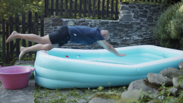 middle aged balding man jumping into a small inflatable pool - balding stock videos & royalty-free footage