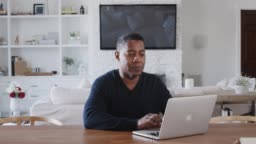 Middle aged black man sitting at a table using laptop computer at home, close up, zoom in
