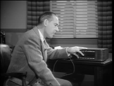 b/w 1948 middle aged businessman talking into intercom/dictaphone on desk in office /it could be you - intercom stock videos and b-roll footage