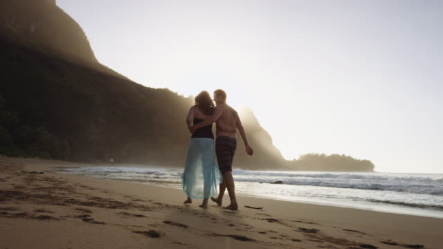 middle aged caucasian couple taking a romantic walk along a beach - na pali coast state park stock videos & royalty-free footage