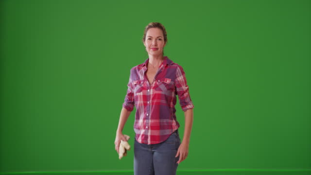 middle aged caucasian woman standing holding gardening gloves on green screen - blond hair stock videos & royalty-free footage