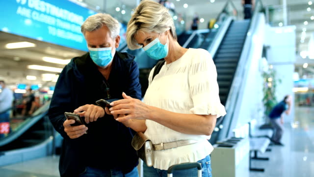 middle aged couple at an airport during coronavirus pandemic. - tourist stock videos & royalty-free footage