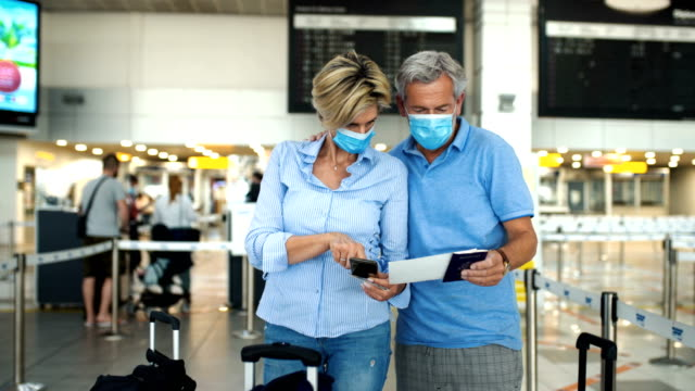 middle aged couple at an airport during coronavirus pandemic. - information medium stock videos & royalty-free footage