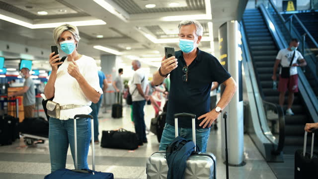 middle aged couple at an airport during coronavirus pandemic. - gate stock videos & royalty-free footage