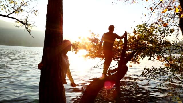 Middle aged couple explore along mountain lake shore