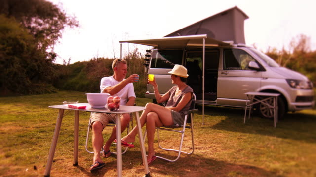 middle aged couple have a drink in front of a camper van. - camper van stock videos and b-roll footage