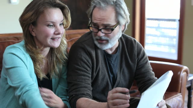 stockvideo's en b-roll-footage met middle aged couple reviewing documents - rapport