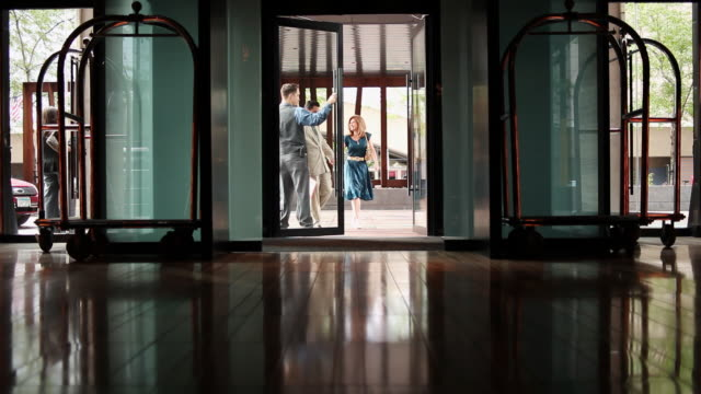 ms middle aged couple walking into lobby of upscale hotel in urban area / minneapolis, minnesota, united states - building entrance stock videos & royalty-free footage