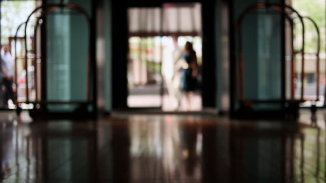 MS R/F Middle aged couple walking into lobby of upscale hotel in urban area / Minneapolis, Minnesota, United States
