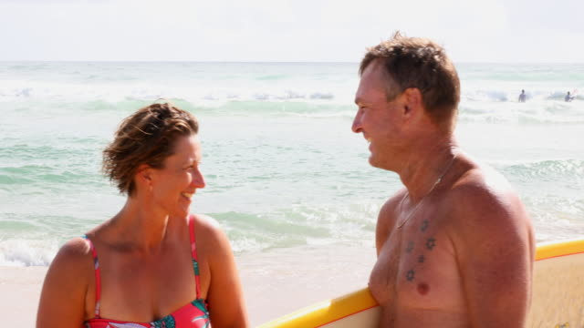 middle aged couple with malibu longboard surfboards - real life stock videos & royalty-free footage