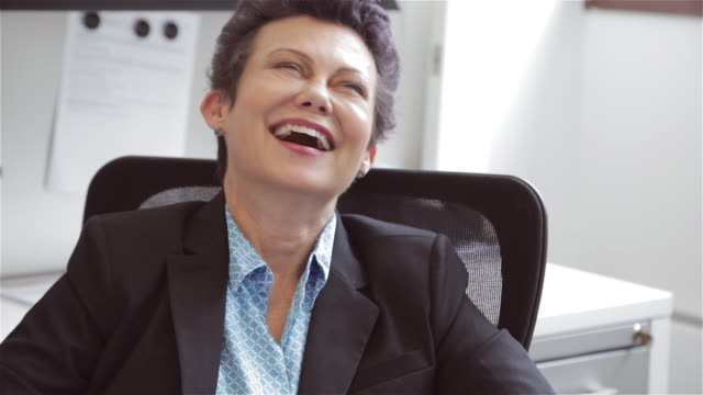 vídeos de stock, filmes e b-roll de middle aged female executive laughs at colleagues' story - só mulheres maduras