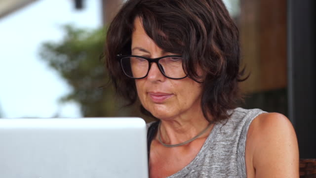 middle aged female freelancer working remotely on laptop - females stock videos & royalty-free footage
