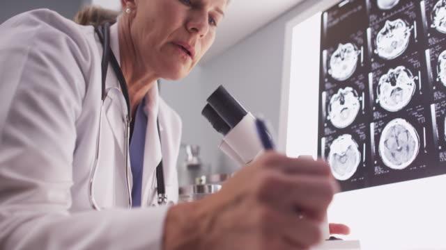 vídeos y material grabado en eventos de stock de middle aged female radiologist looking through microscope - fiabilidad