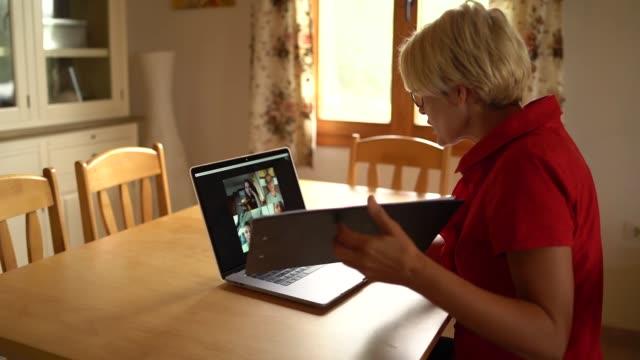 vídeos de stock, filmes e b-roll de uma professora de meia idade explicando online uma lição para seus alunos - distante