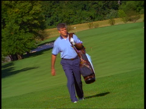 CANTED middle aged male golfer carrying golf bag walking on fairway towards camera