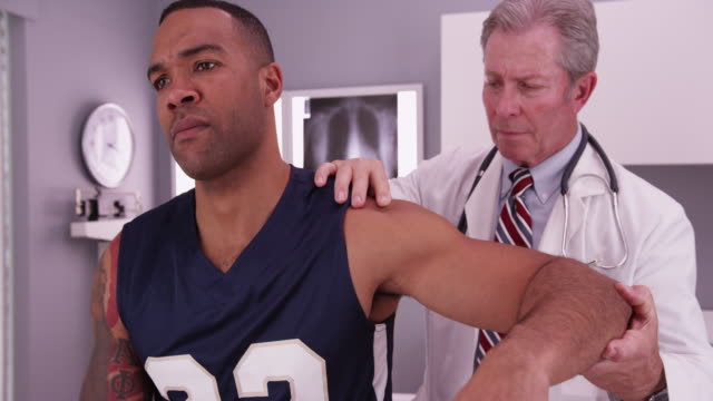 vídeos de stock, filmes e b-roll de middle aged male physician treating young male adult athlete's injury - physical injury