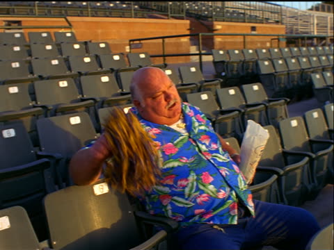 Middle aged man in colorful shirt sitting in empty stadium shaking pom-pom unenthusiastically