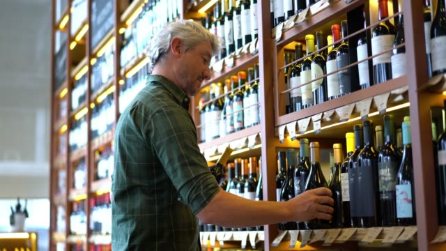 Middle aged man looking at different bottles at a wine store
