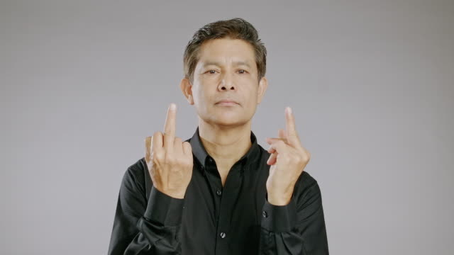 middle aged man portrait in grey background, show two middle finger, aggressive face. - black shirt stock videos & royalty-free footage