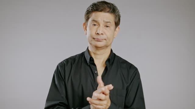 stockvideo's en b-roll-footage met middelbare leeftijd man portret in grijze achtergrond, ongelukkig klappen, boos. - studio shot