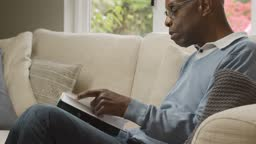 Middle Aged Man Sitting In His Living Room Reading a Book