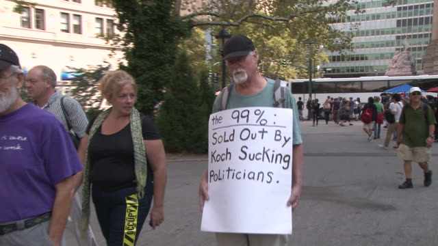 middle aged man walks into battery park wearing a protest sign, on the one year anniversary of the occupy wall street movement. - occupy protests stock videos & royalty-free footage