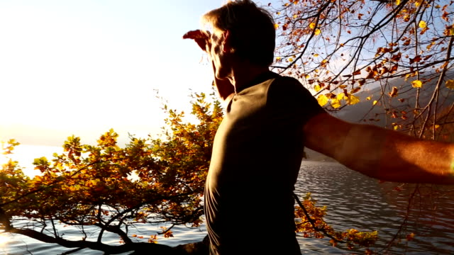 Middle aged man walks up tree trunk over mountain lake