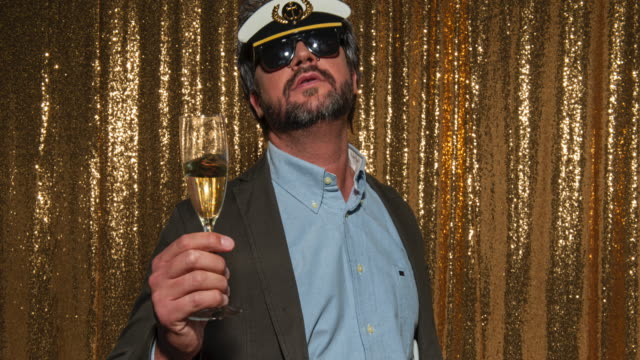 middle aged man wearing a sailor hat and drinking wine while taking photos in the photo booth - sailor hat stock videos & royalty-free footage