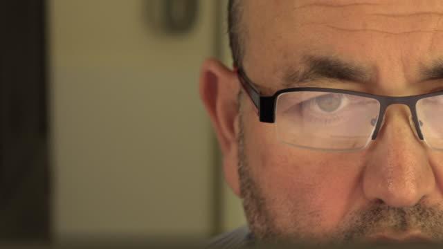 mittleren alter mann mit bart arbeiten mit computer - suspicion stock-videos und b-roll-filmmaterial